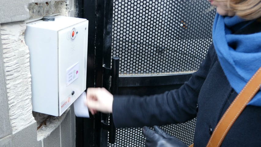 hozzáférés : PARIS, FRANCE - CIRCA 2017: Woman opening secure door with parking ticket by sliding the ship ticket rfid in the card-reader Xerox machine