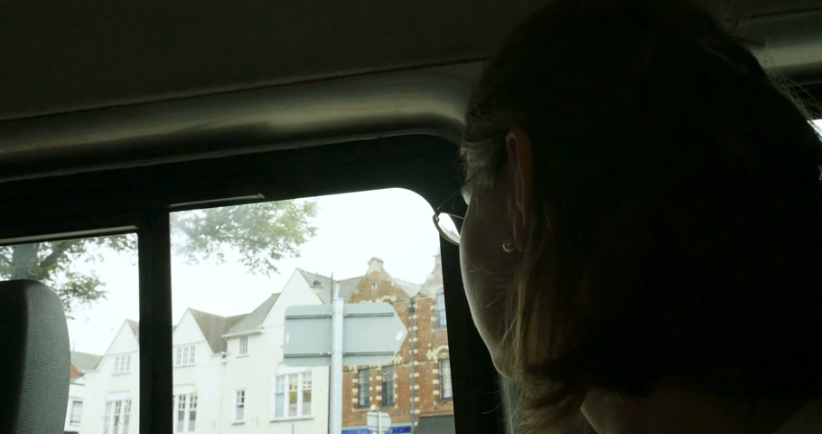 black cab : Elegant Caucasian woman commuting  seating in traditional English taxy cab on a rainy day