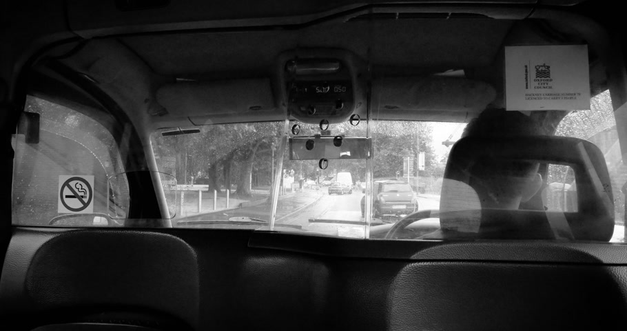 london cab : OXFORD, UNITED KINGDOM - CIRCA 2016: Passenger point of view at the UK diver through security taxy glass  - seating in traditional English taxy cab on a rainy day - black and white