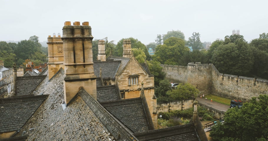 biblioteca : Pan over aerial view over rainy Oxford roofs from the windows of the New College - Oxford university footage.