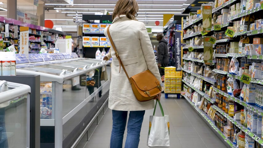 zabkása : PARIS, FRANCE - CIRCA 2017: Supermarket scene with woman walking between rows of supermarket searching for the bio organic products made by European and American manufacturers