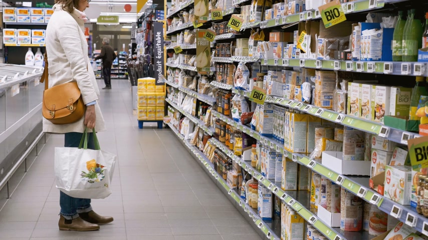 sortimento : PARIS, FRANCE - CIRCA 2017: Supermarket scene with woman walking between rows of supermarket searching for the bio organic products made by European and American manufacturers
