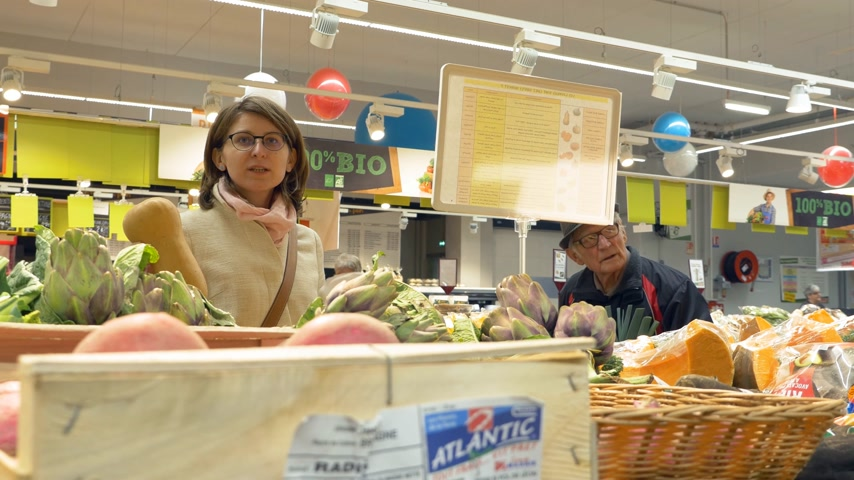 koszyk zakupy : PARIS, FRANCE - CIRCA 2017: Supermarket scene with young French woman and senior man buying fruits and vegetables using the electronic weight Wideo