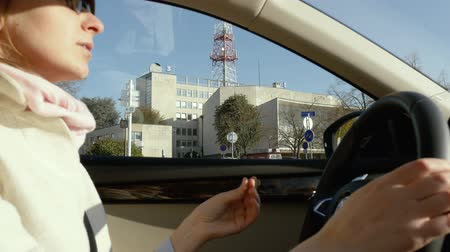 прокат : STRASBOURG, FRANCE - CIRCA 2017: Elegant French woman changing driving in city with France 3 headquarters behind