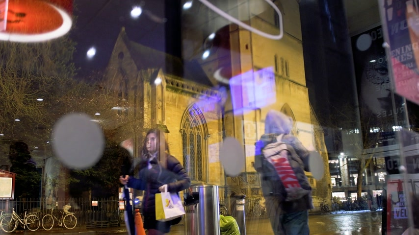 sty : OXFORD UNITED KINGDOM - CIRCA 2017: Busy Magdalen street in oxford with pedestrians and buses walking on a rainy night - view through warm cafe window to the St Mary Magdalen a Church of England parish church in Magdalen Street, Oxford, England. The churc