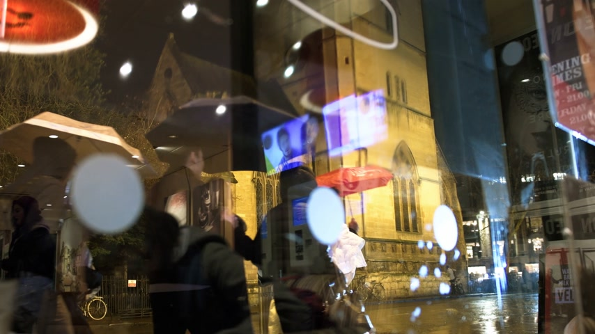 andar : OXFORD UNITED KINGDOM - CIRCA 2017: Busy Magdalen street in oxford with pedestrians and buses walking on a rainy night - view through warm café window to the St Mary Magdalen a Church of England parish church in Magdalen Street, Oxford, England. The churc