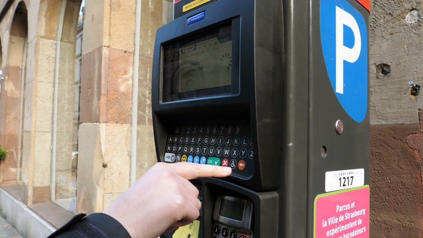 ticket machine : STRASBOURG, FRANCE - CIRCA 2017: Street scene of woman paying for the parking at the teller Parking ticket payment machine in the city - new Qwerty keyboard system being introduced in France to prevent fraud Stock Footage