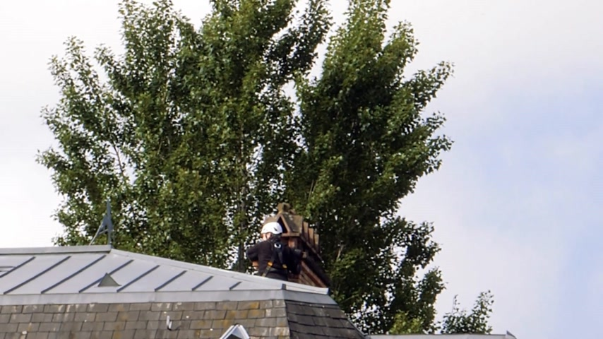 eixo : London, United Kingdom - Circa 2017: Rear view of professional chimney sweeper working on the chimney on a roof top wearing security helmet and protection Stock Footage