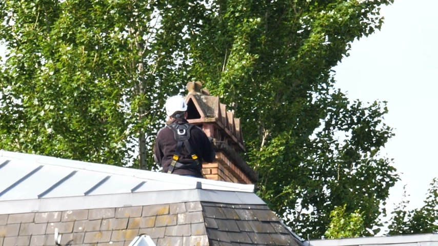 maszat : Rear view of unrecognizable chimney sweeper working on the chimney on a roof top wearing security helmet and protection Stock mozgókép