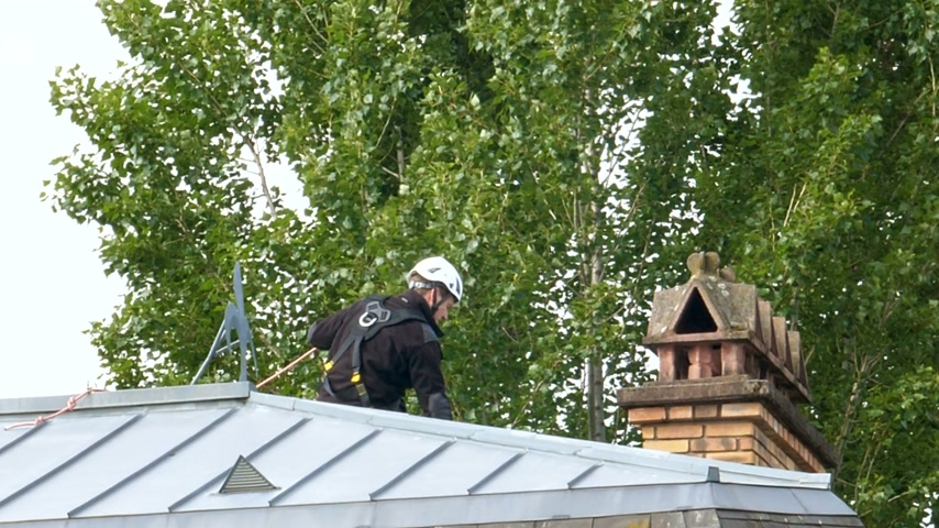 maszat : London, United Kingdom - Circa 2017: Rear view of chimney sweeper working on the chimney on a roof top wearing security helmet and protection Stock mozgókép