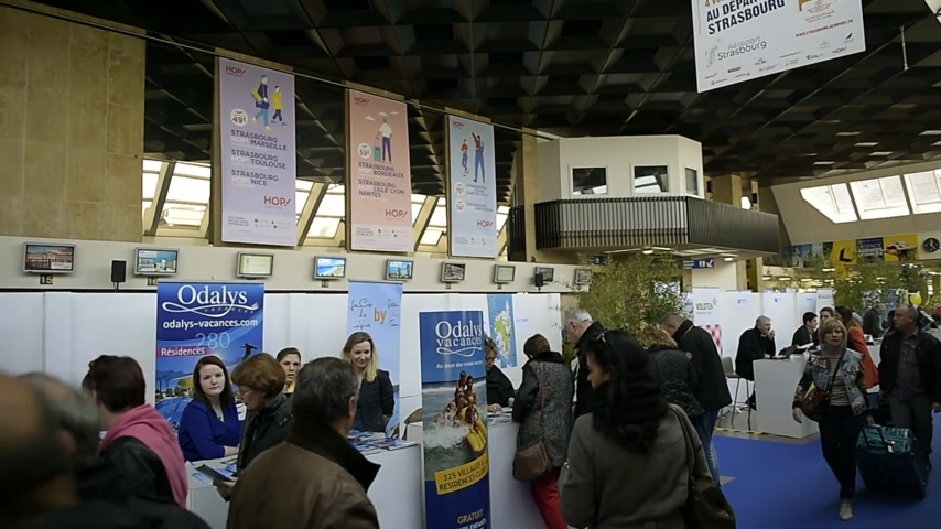 geçen : Strasbourg, FRANCE - CIRCA 2017: Interior of Entzheim Strasbourg International Airport with commuters looking at the offers of the holiday travel fair organized inside the airport with diverse offers to visit the globe Stok Video