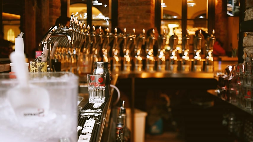 fabricado cerveja : PARIS, FRANCE - CIRCA 2016: Front view of young beautiful female bartender brining beer preparing cocktails  for client at bar - tilt-shift lens to make beautiful silhouette and for moody atmosphere
