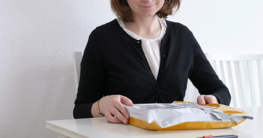 post room : PARIS, FRANCE - CIRCA 2017: Woman looking at the DHL Flyer yellow parcel with the goods she bought online unboxing unpacking