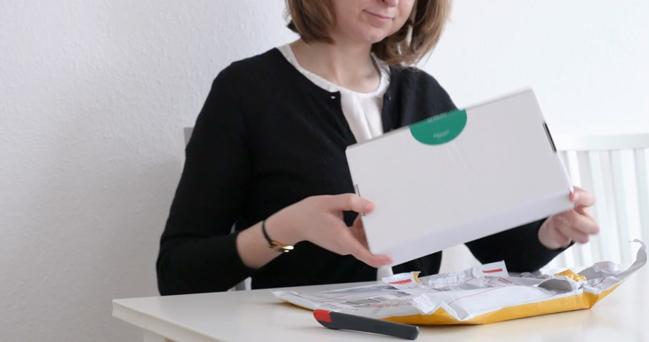 post room : PARIS, FRANCE - CIRCA 2017: Woman opening DHL yellow parcel plastic film containing white box with luxury paper items inside unboxing un packing