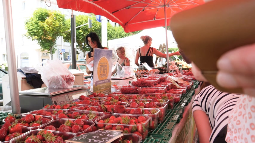 satılık : Strasbourg, France - circa 2017: Farmers selling to customers strawberries at the traditional French farmer market in Strasbourg - buying Alsace cherries organic bio food