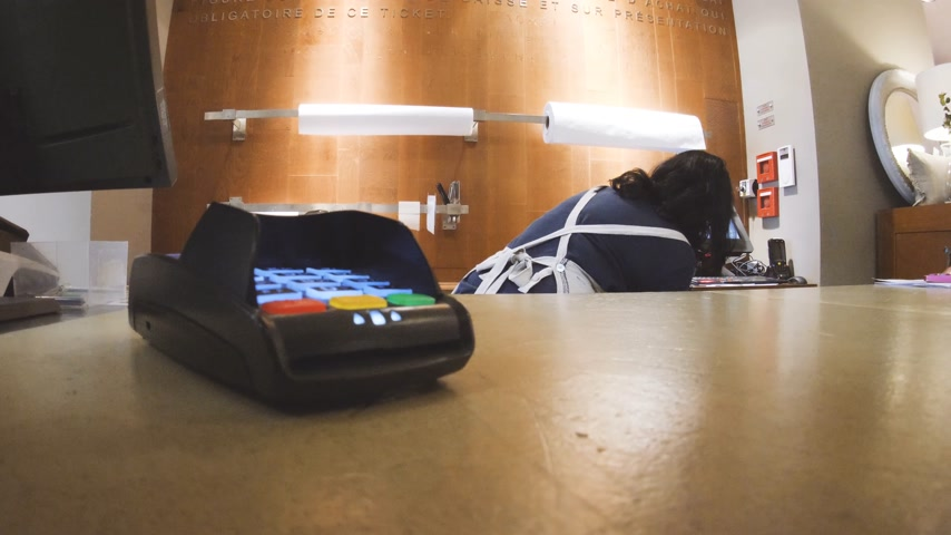 card pin : Paris, France - Circa 2017: Caucasian man playing with credit card reader paying terminal in store while black ethnicity woman preparing the gift he bought with the credit card Stock Footage
