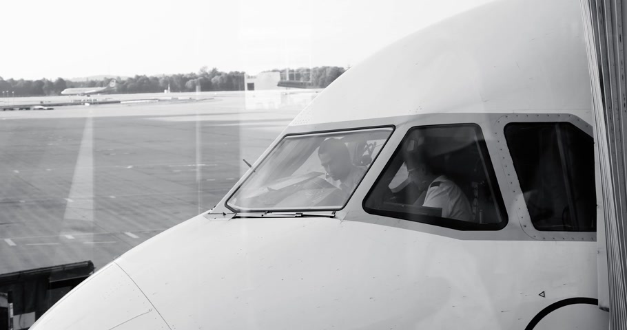 kaptan : MUNICH, GERMANY - CIRCA 2017: Airplane captain and his co-pilot discussing in cockpit about last instructions and flight route before taking off from international airport in Germany people black and white Stok Video