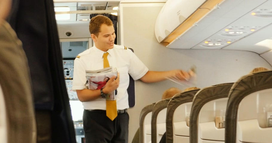 steward : FLIGHTS LONDON - USA - CIRCA 2017: Steward serve the passengers of the business class inside Airbus A 319-100 airplane operated by Lufthansa Airlines with fresh newspapers and magazines. Serve press and news  in the passenger cabin