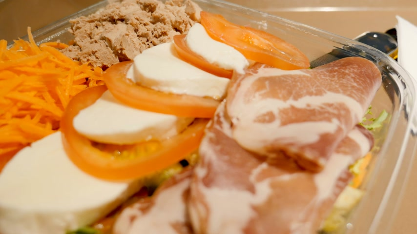 olive oil pour : Delicious ready to eat salad on a cafe tray in airport - ready-to-eat salad box with cheese, carrots, meat, mozzarella, tomatoes and prosciutto and salad leaves Stock Footage
