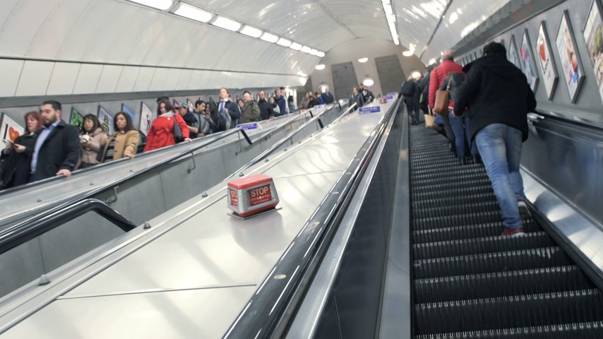 train tunnel : London, United Kingdom - Circa 2017: London Underground tube station with crowd of people on escalator during rush hour going to work or home commuting in London British transportation London Tube