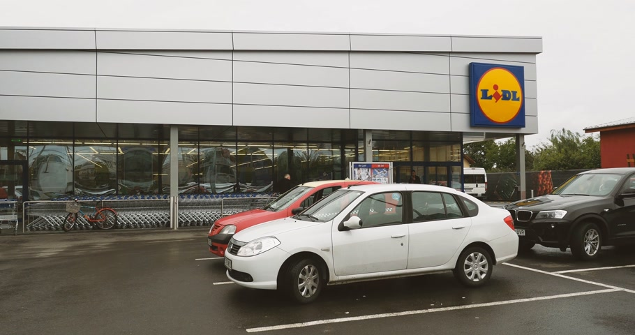 parkoló : BUCHAREST, ROMANIA - CIRCA 2017: Lidl Supermarket building entrance seen from the parking with customers entering store. Lidl is a German global discount supermarket chain, based in Neckarsulm, Germany