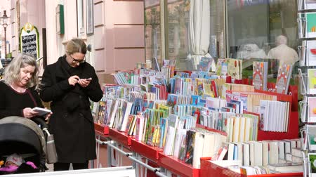 troli : RASTATT, GERMANY - CIRCA 2017: German mothers buying child children books at the outdoor market shelf in German city of Rastatt