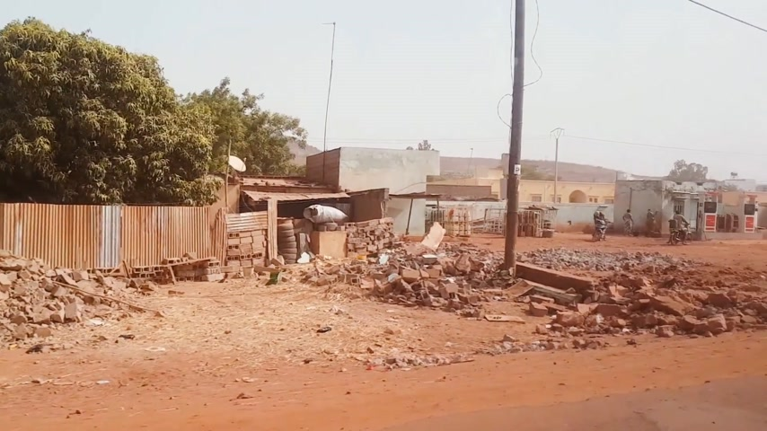 niger : BAMAKO, MALI - CIRCA 2017: View from the humanitarian mission transportation vehicle of the poor street of the Bamako, people commuting near the destroyed buildings, selling goods etc.