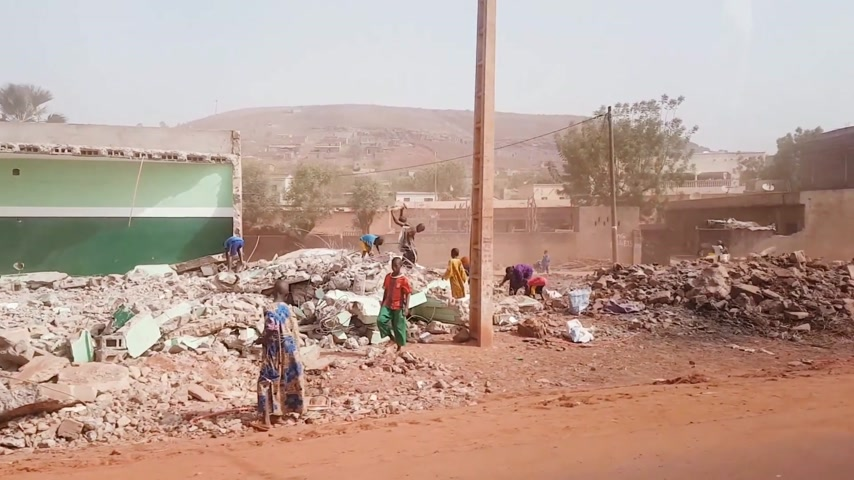 elpusztított : BAMAKO, MALI - CIRCA 2017: View from the humanitarian mission transportation vehicle of the poor street of the Bamako, people commuting near the destroyed buildings with childrens working on the disassembling the bricks