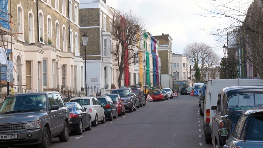 portobello road : LONDON, UNITED KINGDOM - CIRCA 2017: Colorful houses on Bassing Street London, not so far from Portobello market on a warm summer day with cars parked nearby