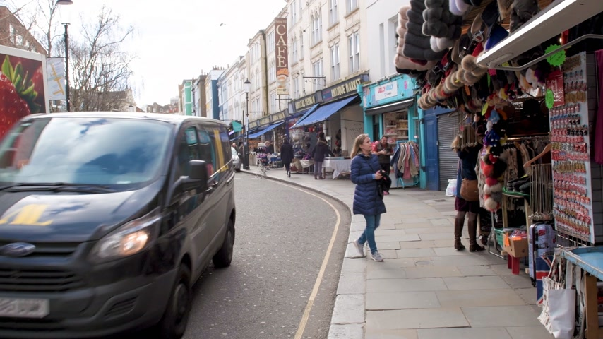portobello road : London, United Kingdom - Circa 2017: Perspective view over famous Portobello market road in Notting hill London early in the morning with locals and tourists sightseeing