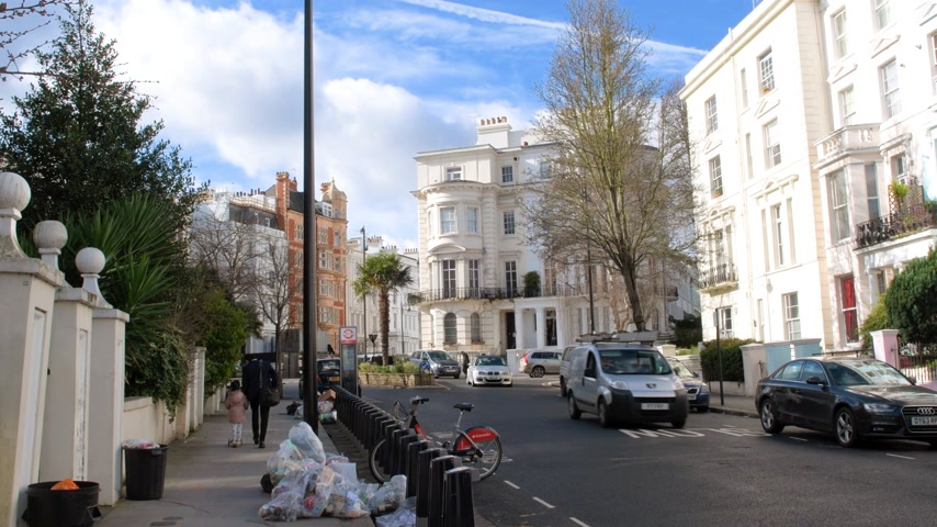 gürcü : London, United Kingdom - Circa 2017: Expensive townhouses and other real estate in London on a warm spring day with cars and pedestrians commuting Stok Video