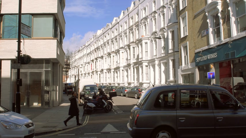 hackney carriage : London, United Kingdom - Circa 2017: Expensive townhouses and other real estate in London on a warm spring day with cars and pedestrians commuting Stock Footage