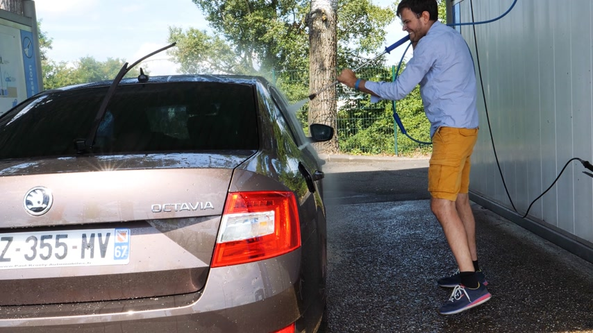 lathering : PARIS, FRANCE - CIRCA 2017: Rear view of French man washing car in self service car wash with the high pressure water pump making rainbow - removing dirt from the Skoda Octavia car