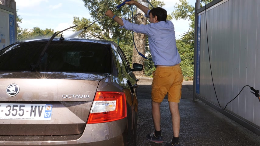 lathering : PARIS, FRANCE - CIRCA 2017: Rear view of man wearing sand shorts washing car in self service car wash with the high pressure water pump making rainbow - removing dirt from the Skoda Octavia car