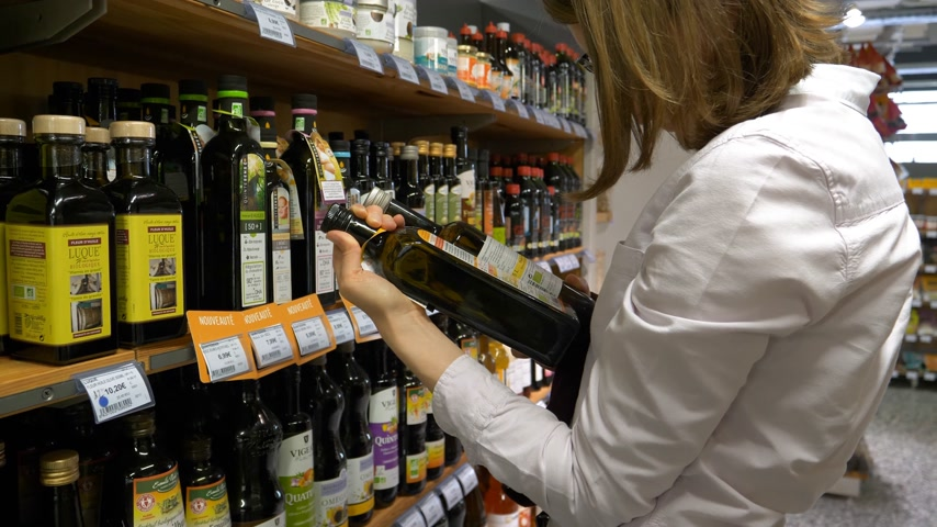 shops : PARIS, FRANCE - CIRCA 2017: French woman buying Bio Organic Olive Colza Walnuts Oil comparing the bootless - choosing the best product from the Organic Bio supermarket shelf