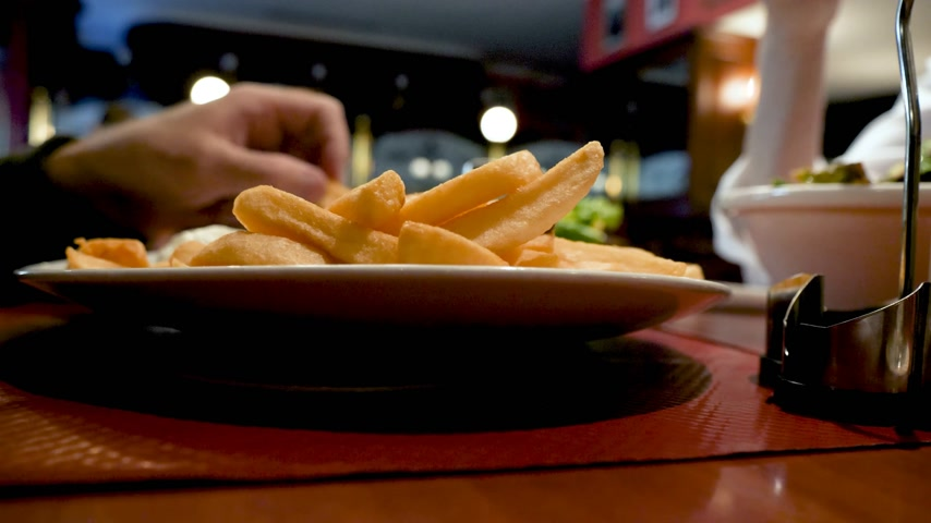 frites : Side view of couple eating in cafe restaurant delicious French fries and fresh leaves ice-berg French salad