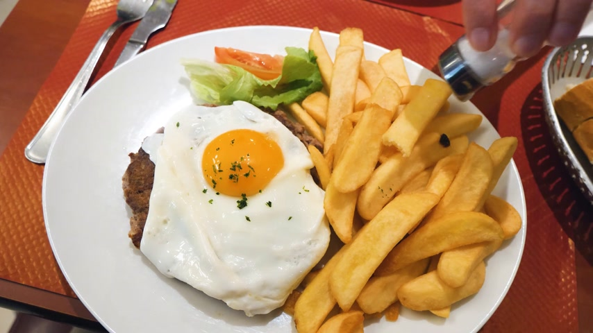 frites : Rotation over delicious burger meat with yellow yolk and French fries. Tasty food in French cafe restaurant