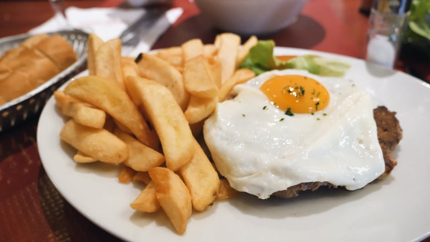 frites : Woman eating stealing delicious burger meat with yellow yolk and French fries. Tasty food in French cafe restaurant Stock Footage
