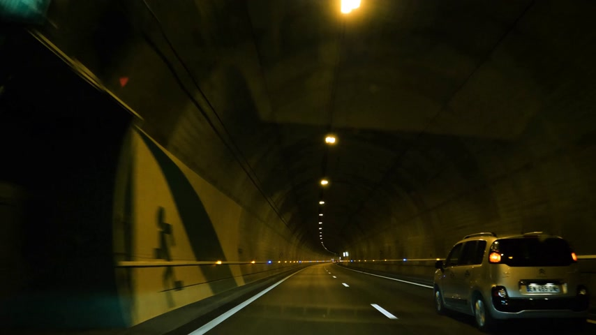 citroen : Zurich Switzerland - Circa 2017: Driver point of view driving fast in the illuminated endless tunnel with reinforced security signs and ventilation tubes fans - Citroen mini van driving Stock Footage