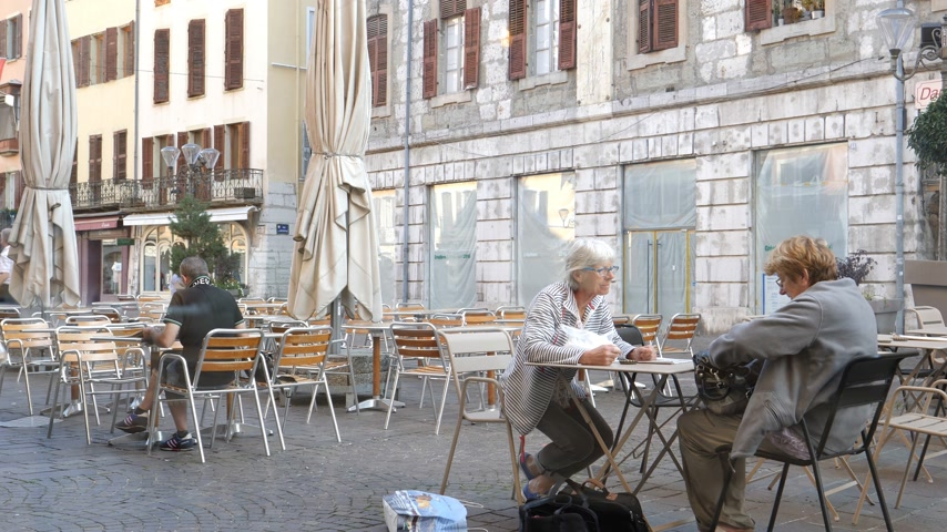 alpes : CHAMBERY, FRANCE - CIRCA 2017 Two senior women talking on the cafe outdoor terrace in central square early in the morning in front of Ernest cafe Place Saint-Leger