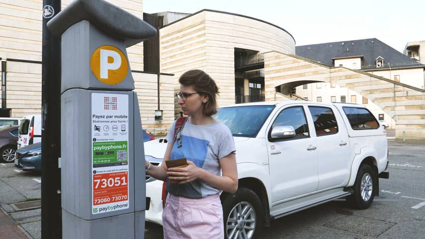 bilet : CHAMBERY, FRANCE - CIRCA 2017, Woman paying for parking at the machine ATM for the white large SUV jeep parked behind her in central Chambery with Espace Malraux in the background