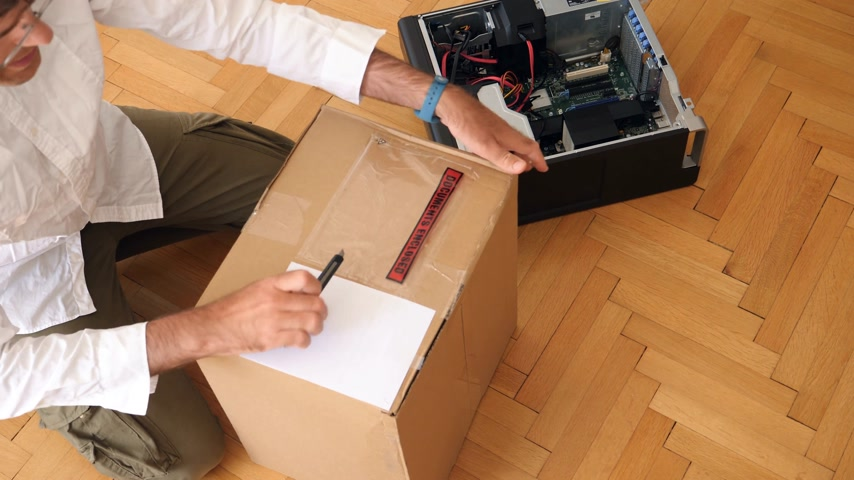 cardíaco : LONDON, UNITED KINGDOM - CIRCA 2017: Computer geek unboxing cardboard box with Documents Enclosed slip and bubble warp next to powerful Dell Workstation Server Dell Precision lying on the floor