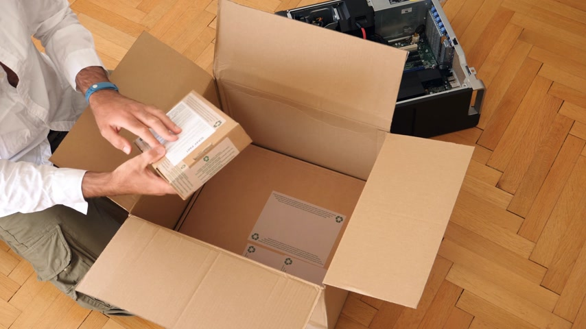 iş istasyonu : LONDON, UNITED KINGDOM - CIRCA 2017: Computer geek unboxing unpacking cardboard box with bubble warp and two cardboard box next to powerful Dell Workstation Server Dell Precision lying on the floor
