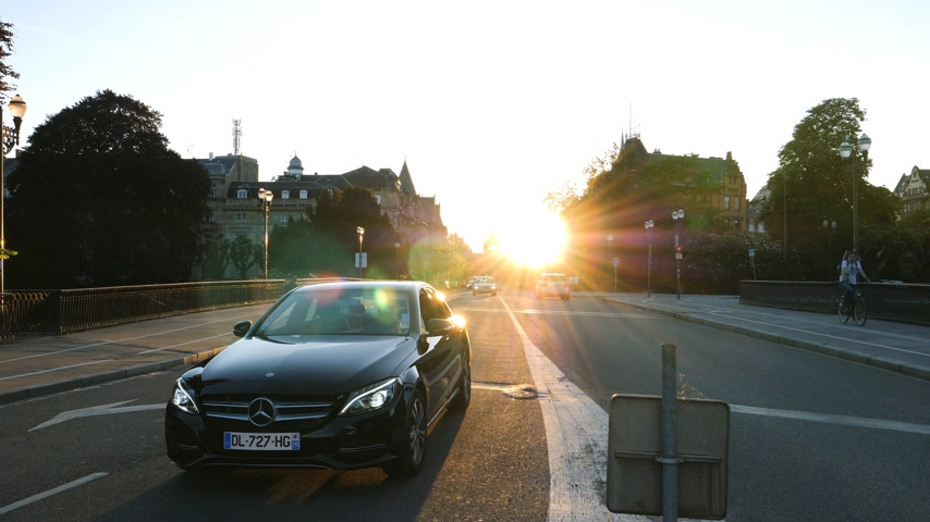 sokak lâmbası direği : STRASBOURG, FRANCE - CIRCA 2017: Vide view of avenue de la Liberte with impressive view of the Palais du Rhin at sunset and Luxury Mercedes-Benz car waiting for the green light, Sun flare sunlight