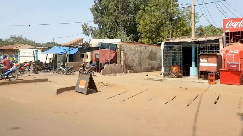 niger : BAMAKO, MALI - CIRCA 2017: View from the humanitarian mission transportation vehicle of the poor street of the Bamako, people commuting on motorcycles, stores opened, people shopping