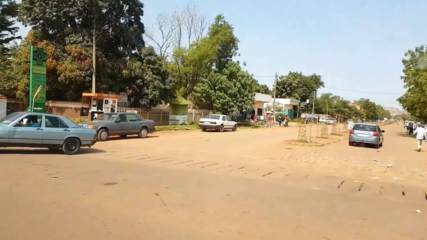 niger : BAMAKO, MALI - CIRCA 2017: Fast motion time-lapse view from the humanitarian mission transportation vehicle of the poor street of the Bamako, black ethnicity people commuting on motorcycles shopping street