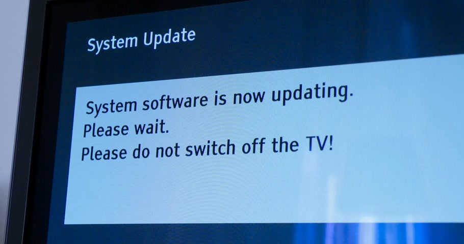 угождать : London, United Kingdom - Circa 2017: Zoom out from Panasonic Viera message of system update software process on a  television set in living room message System software updating, please wait. Please do not switch off your tv.