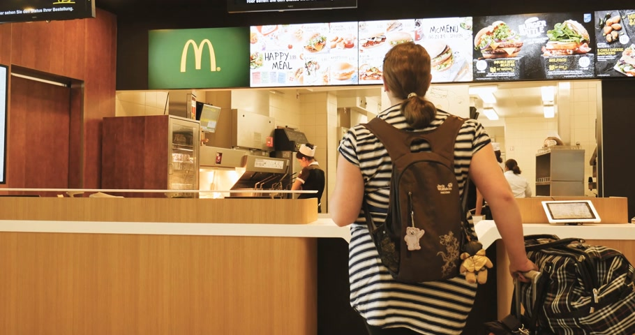 wozek dzieciecy : FRANKFURT, GERMANY - CIRCA 2017: Interior of McDonalds fast food restaurant with female workers preparing the orders for the overweight mother with pram baby stroller