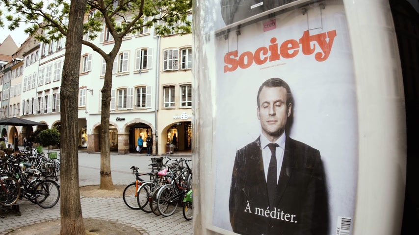 french president : Strasbourg, France - Circa 2017: Emmanuel Macron French President on the cover of the Society Magazine with the message To Meditate - Strasbourg Press kiosk city France people walking summer day