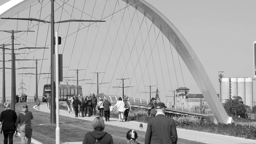 d day : STRASBOURG, FRNACE - CIRCA 2017: Black and white of pedestrians looking walking toward the new tramway and new bridge Pont-tramway Citadelle inauguration in 2017 for tramway line D